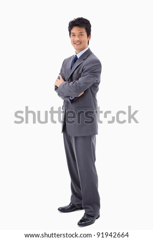 Portrait of a smiling businessman with the arms crossed against a white background