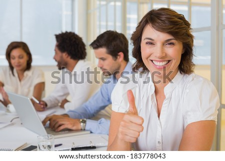 Portrait of a smiling businesswoman gesturing thumbs up with colleagues in meeting at the office