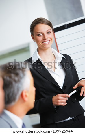 Portrait of a smiling businesswoman giving a presentation at work - stock photo