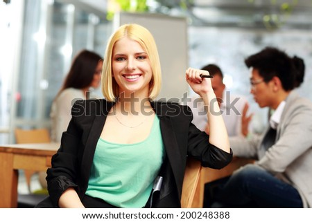 Portrait of a smiling businesswoman in office, with her colleagues in background