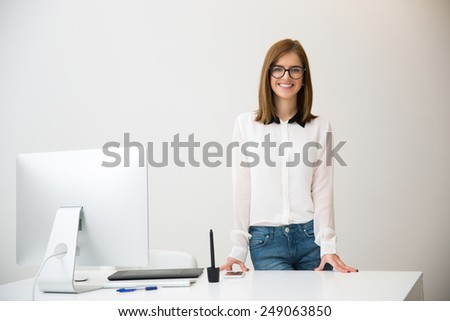 Portrait of a smiling businesswoman standing in office - stock photo