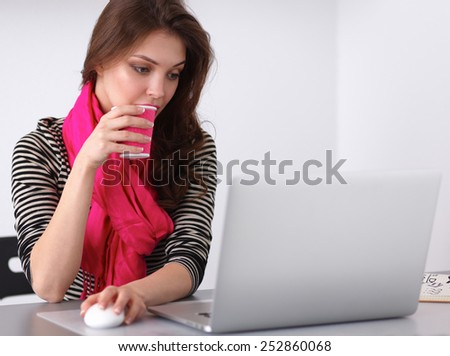 Portrait of a smiling businesswoman with coffee cup in front laptop - stock photo
