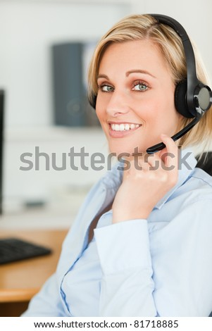 Portrait of a smiling businesswoman with headset looking into camera in her office
