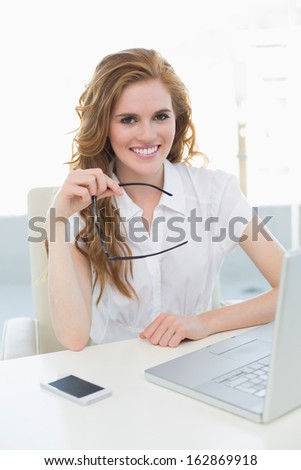 Portrait of a smiling businesswoman with laptop sitting at desk in a bright office