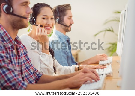 Portrait of a smiling businesswoman working with colleagues in a call centre - stock photo