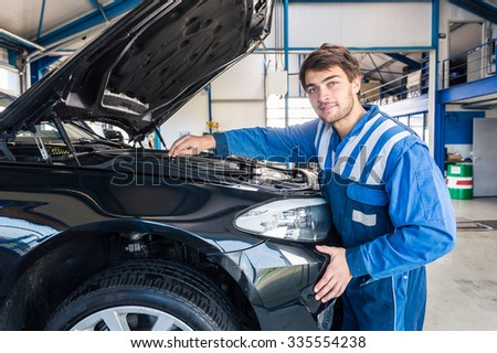 Portrait of a smiling car mechanic looking under the hood of a car - stock photo