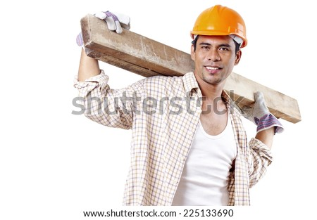 Portrait of a smiling carpenter carrying lumber in his shoulder. - stock photo