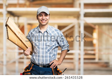 Portrait of a smiling carpenter holding wood planks in a construction site - stock photo