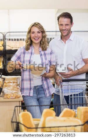 Portrait of a smiling casual couple taking a bread in supermarket