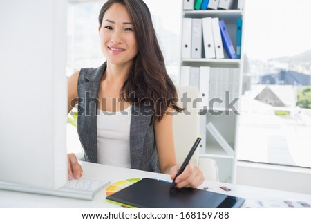 Portrait of a smiling casual female photo editor using graphics tablet in a bright office - stock photo