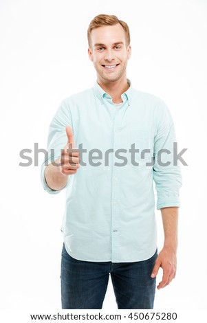 Portrait of a smiling casual man showing thumb up and looking at camera over white background - stock photo