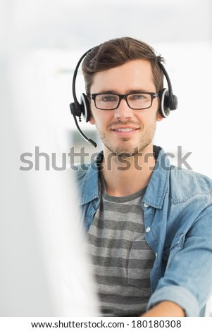 Portrait of a smiling casual young man with headset using computer in a bright office - stock photo