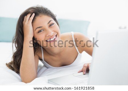 Portrait of a smiling casual young woman using laptop in bed at home