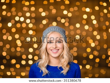 Portrait of a smiling charming woman looking at camera over holidays lights background - stock photo