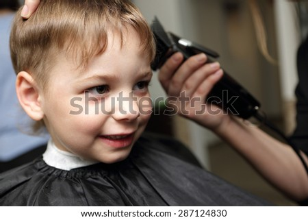 Portrait of a smiling child at the barbershop - stock photo