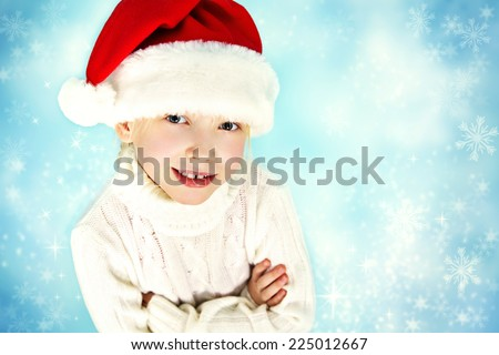 portrait of a smiling child in a Santa hat and sweater