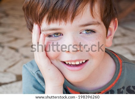 Portrait of a smiling child with his hand on his face - stock photo
