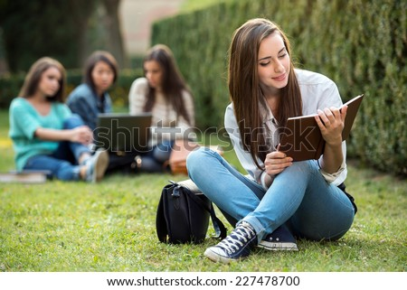 Portrait of a smiling college girl is holding book with blurred students are sitting in the park. - stock photo