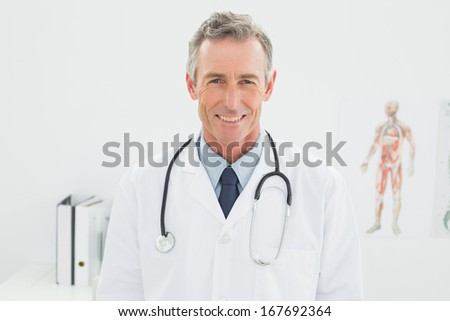 Portrait of a smiling confident male doctor standing in the medical office