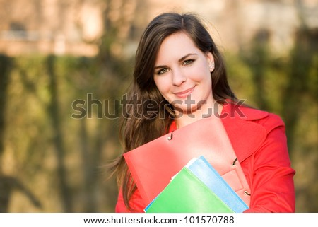 Portrait of a smiling confident young student woman in bright red coat. - stock photo