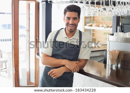 Portrait of a smiling confident young waiter standing at the cafe counter - stock photo