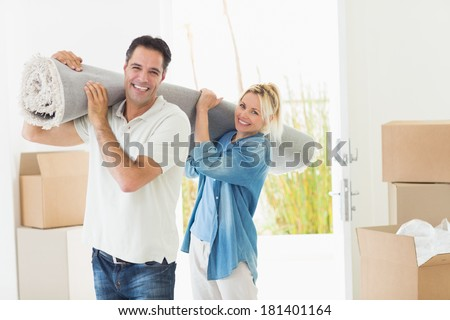 Portrait of a smiling couple carrying rolled rug after moving in a house - stock photo