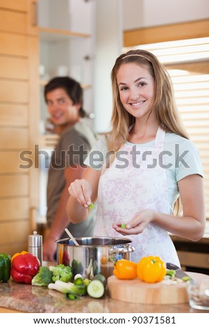 Portrait of a smiling couple cooking in their kitchen - stock photo