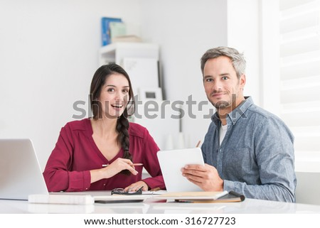 Portrait of a smiling couple doing their accounting A dark hair braided woman and a grey hair man with beard holding a tablet are looking at camera, sitting at a table with a laptop in front of them