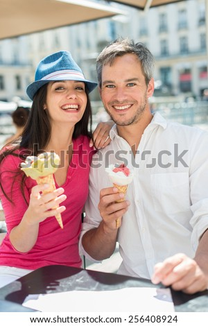 Portrait of a smiling couple eating ice cream in the city. The grey hair man with a beard is in a white shirt. The woman is wearing a blue hat and a pink top.