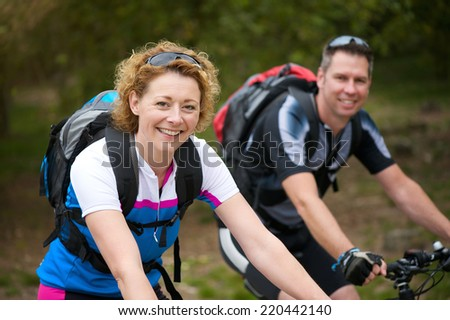 Portrait of a smiling couple enjoying a bicycle ride outdoors - stock photo