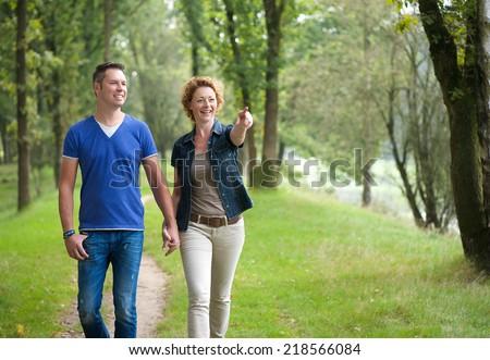 Portrait of a smiling couple enjoying a walk outdoors - stock photo