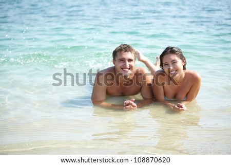 Portrait of a smiling couple lying in warm water