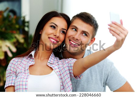 Portrait of a smiling couple making selfie photo with smarphone - stock photo