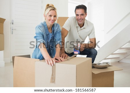 Portrait of a smiling couple packing boxes in a new house