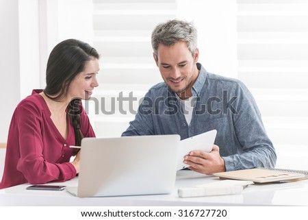 Portrait of a smiling couple planning their next trip, the grey hair man is showing something to his braided hair wife on the tablet. They are sitting at a white table with a laptop in front of them - stock photo