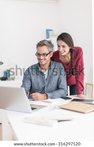 Portrait of a smiling couple planning their next trip, the grey hair man with beard and glasses is sitting at the table searching the internet on their laptop and wife is looking over his shoulder