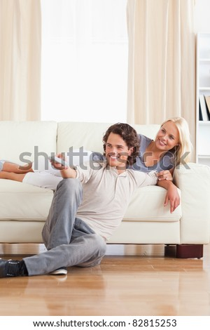 Portrait of a smiling couple watching TV in their living room