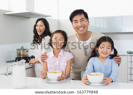 Portrait of a smiling couple with happy two daughters having breakfast in the kitchen at home