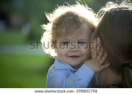 Portrait of a smiling curly baby boy hugging mom carefully with love outdoor closeup, horizontal photo - stock photo