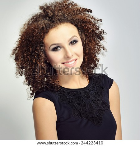 Portrait of a smiling curly haired woman - stock photo