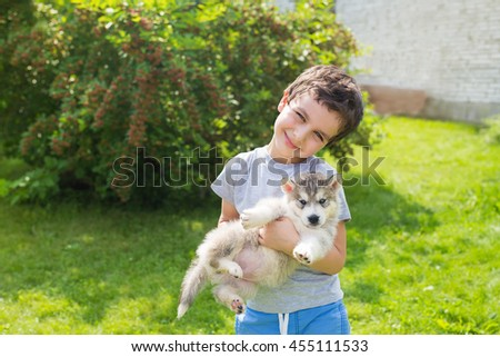 Portrait of a smiling cute little boy with a angry husky puppy