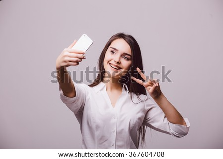 Portrait of a smiling cute woman making selfie photo on smartphone isolated on a gray background - stock photo