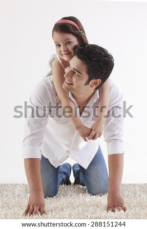 Portrait of a smiling daughter sitting on her father's back - stock photo