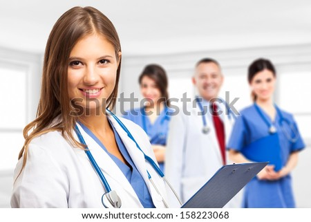 Portrait of a smiling doctor in front of her team