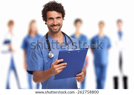 Portrait of a smiling doctor in front of his medical team - stock photo