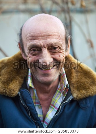 Portrait of a smiling elderly man outdoors closeup