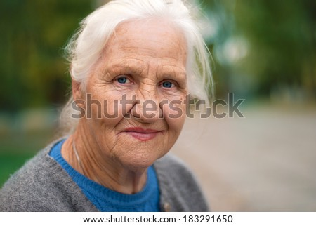 Portrait of a smiling elderly woman. A photo on the nature background  - stock photo