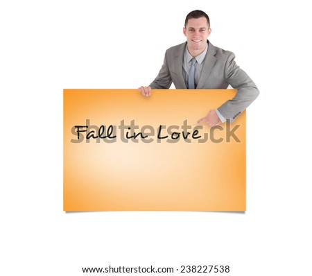 Portrait of a smiling entrepreneur pointing at something against orange card