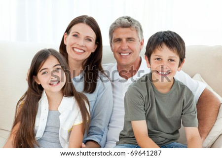 Portrait of a smiling family at home. Focused on children - stock photo