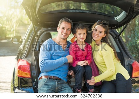 Portrait of a smiling family sitting in the trunk of their car on a country road. They are leaving for the weekend. They are wearing sunglasses and colored pulls. The girl is about seven years old